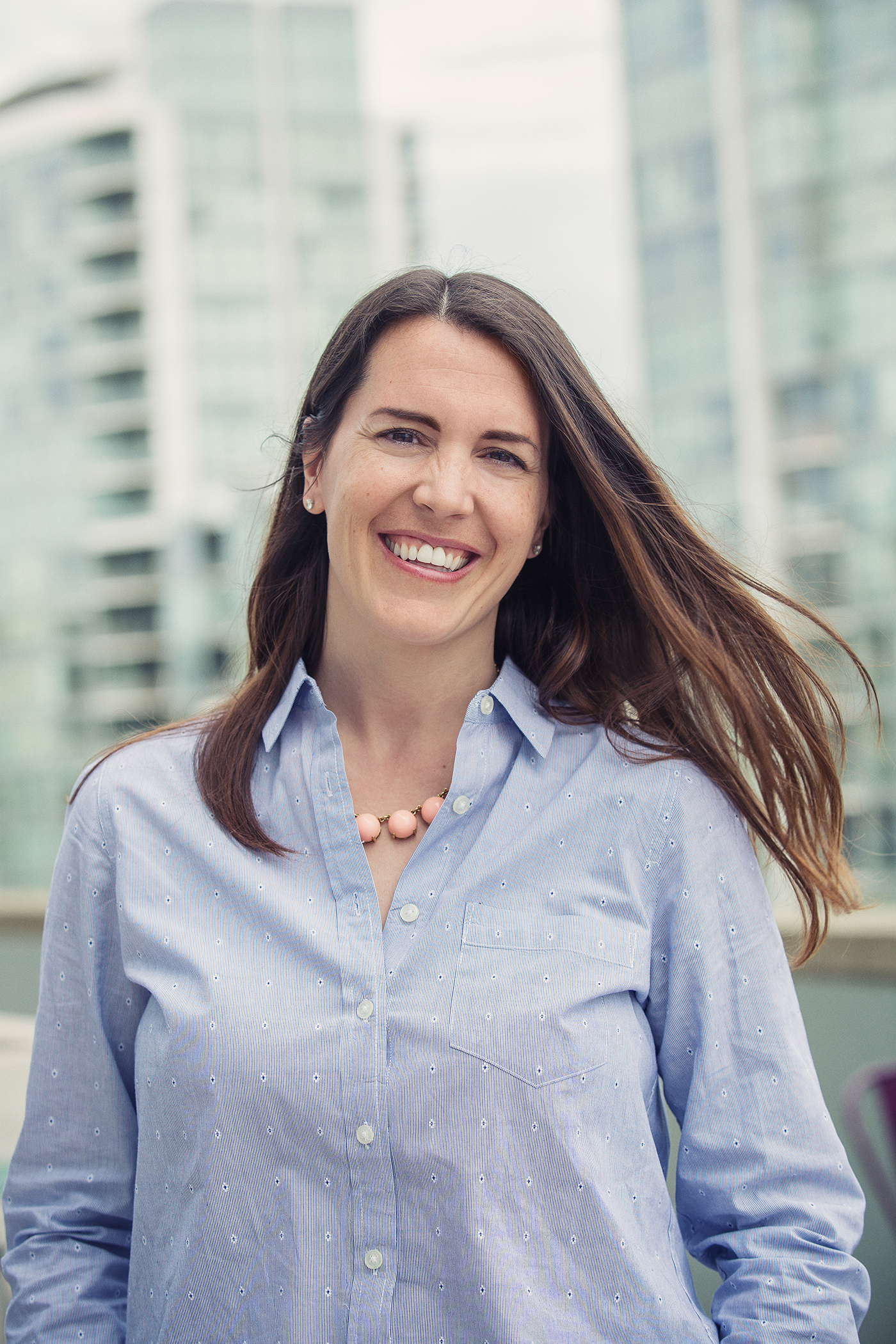 San Francisco tech professional portrait, smiling woman, blurred city background